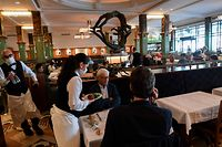People have lunch at the restaurant La Coupole in Paris, on June 15, 2020, as cafes and restaurants are allowed to serve customers inside, as well as on terraces, as part of the easing of lockdown measures taken to curb the spread of the COVID-19 pandemic, caused by the novel coronavirus. (Photo by ALAIN JOCARD / AFP)