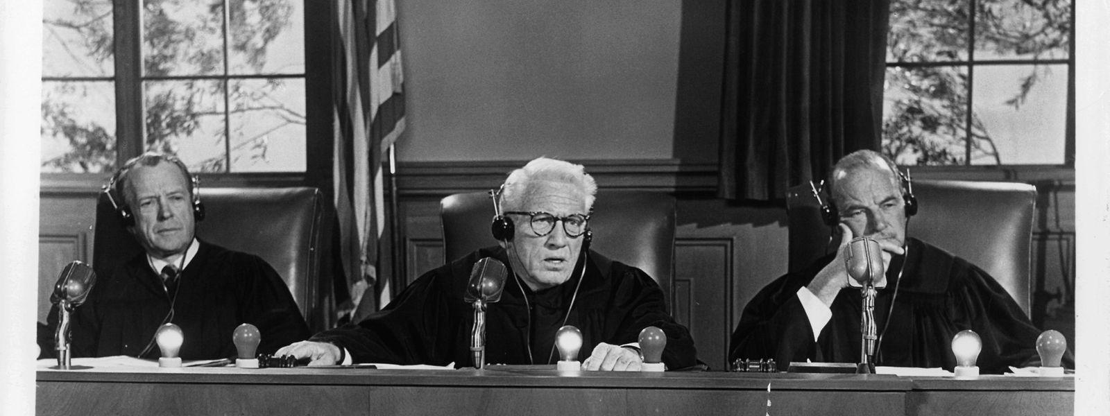 """Die drei von Kenneth MacKenna, Spencer Tracy und Ray Teal (von links) gespielten Richter hören im Film """"Judgment at Nuremberg"""" einer Zeugenvernehmung zu."""