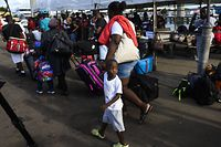 "Evacuees wait to board a bus heading to an evacuation shelter after getting off a ferry from Marsh Harbour on Abaco island in the aftermath of hurricane Dorian in Nassau, Bahamas on September 9,2019 - President Donald Trump said Monday that the US would have to be careful about allowing Bahamian survivors of Hurricane Dorian into the country, warning there could be ""very bad people"" among them. The previous day, several hundred storm survivors were prevented from boarding a ferry from the Bahamas to Florida because they lacked US visas -- an incident that a top American immigration official said was a mistake. (Photo by ANDREW CABALLERO-REYNOLDS / AFP)"