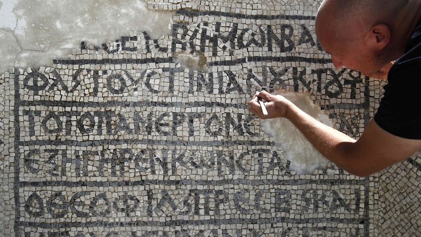 An archaeologist works on part of a 1,500-year-old mosaic floor bearing the names of Byzantine Emperor Justinian.