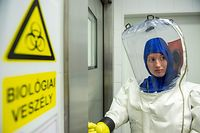 A scientist wearing her Personal protective equipment (PPE) enters the lab at the Szentgothai Research Center of Pecs University, in Pecs, Hungary on May 13, 2020 during their diagnostic activity to locate the nature of the virus strain and the connection to novel coronavirus COVID-19. (Photo by KAROLY ARVAI / POOL / AFP)