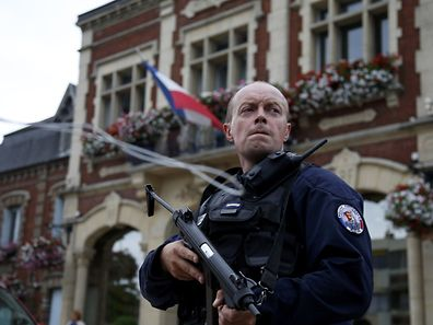 A policeman secures a position in front of the city hall after two assailants had taken five people hostage in the church at Saint-Etienne-du -Rouvray near Rouen in Normandy, France, July 26, 2016. Two attackers killed a priest with a blade and seriously wounded another hostage in a church in northern France on Tuesday before being shot dead by French police.   REUTERS/Pascal Rossignol