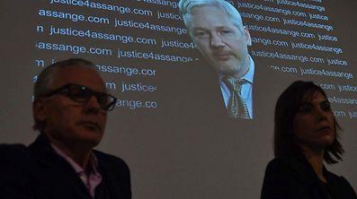 M. Assange est apparu sur un écran géant lors d'une conférence de presse organisée par ses avocats, le teint pâle, en cravate, barbichette et cheveux blancs.