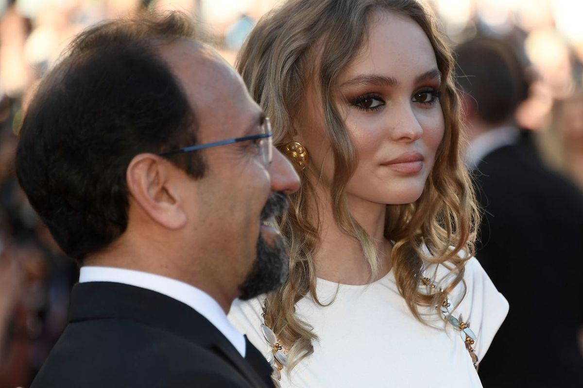 Lily-Rose Depp (R) and Iranian director Asghar Farhadi pose as they arrive on May 17, 2017 for the screening of the film 'Ismael's Ghosts' (Les Fantomes d'Ismael) during the opening ceremony of the 70th edition of the Cannes Film Festival in Cannes, southern France.  / AFP PHOTO / Anne-Christine POUJOULAT