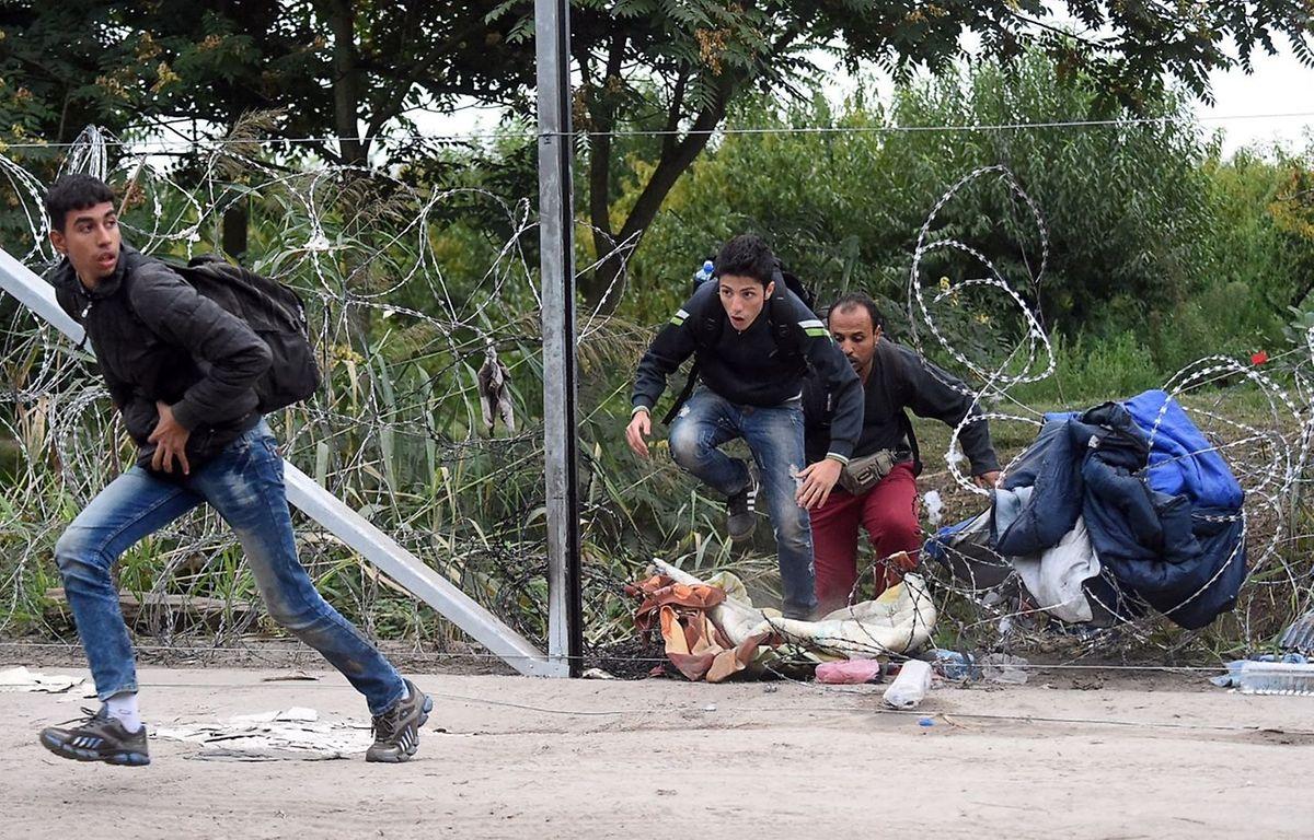 Refugiados e migrantes a forçarem a fronteira húngara