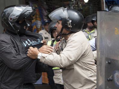 "TOPSHOT - CORRECTION - A Venezuelan pro-government supporter scuffles with police personnel in riot gear during a protest in front of the Supreme Court in Caracas on March 31, 2017.  Venezuela's attorney general Luisa Ortega surprisingly broke ranks with President Nicolas Maduro on Friday, condemning recent Supreme Court rulings that consolidated the socialist president's power as a ""rupture of constitutional order."" / AFP PHOTO / STR / �The erroneous mention[s] appearing in the metadata of this photo by STR has been modified in AFP systems in the following manner: [A Venezuelan pro-government supporter scuffles with police ] instead of [Venezuelan opposition activists scuffle with National Guard]. Please immediately remove the erroneous mention[s] from all your online services and delete it (them) from your servers. If you have been authorized by AFP to distribute it (them) to third parties, please ensure that the same actions are carried out by them. Failure to promptly comply with these instructions will entail liability on your part for any continued or post notification usage. Therefore we thank you very much for all your attention and prompt action. We are sorry for the inconvenience this notification may cause and remain at your disposal for any further information you may require.�"