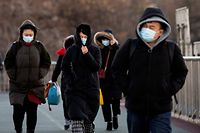 People wrapped up due to freezing weather walk on an overpass in Beijing on January 6, 2021, as the Chinese capital experiences record low temperatures. (Photo by NOEL CELIS / AFP)