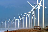 """Villagers are dwarfed by giant windmills built by the Danish Development Agency, DANIDA, along the shores of Bangui, Ilocos Norte province in northern Philippines Wednesday Nov. 8, 2006. The sixteen giant """"Bangui Windmills"""" built last year, are capable of generating 54 Megawatts of electricity and are the first such alternative source of energy in Southeast Asia. (AP Photo)"""
