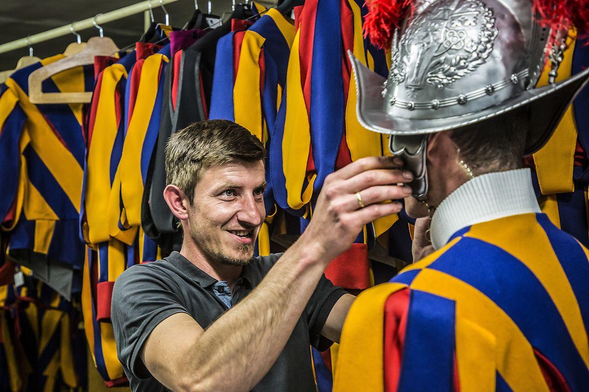 Schmied Johann Schmidberger steht in der Waffenkammer der Päpstlichen Schweizergarde im Vatikan und prüft bei einem Gardisten die Passform seiner Helme.