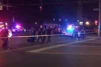 This videograb taken from the Twitter account of Derek Myers on August 4, 2019 shows police officers walking behind police cordon following a mass shooting in the popular bar and nightlife Oregon district in Dayton, Ohio. - Nine people were killed in a mass shooting early on August 4 in Dayton, Ohio, police said, adding that the assailant was shot dead by responding officers. (Photo by Derek MYERS / @DerekMyers Twitter account / AFP)