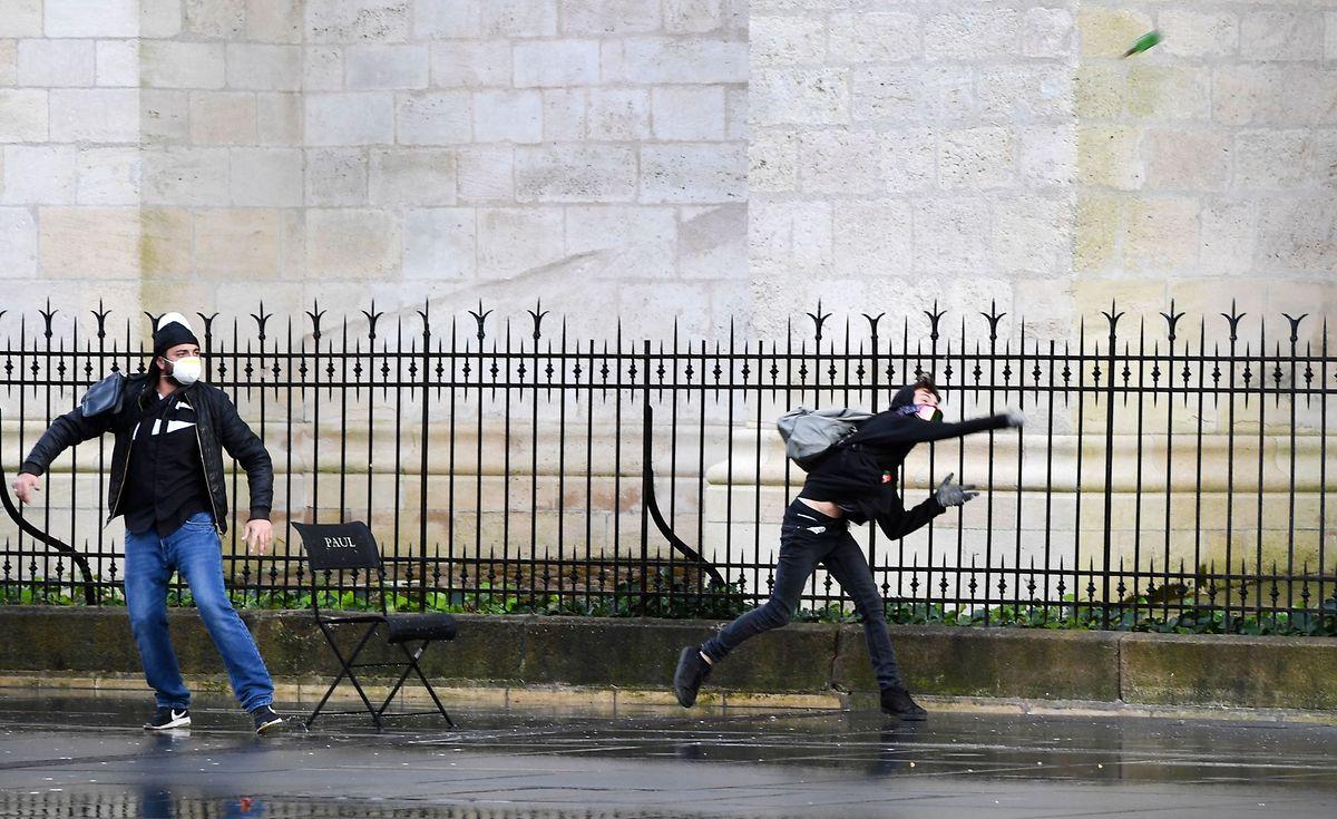 Einer der Demonstranten in Bordeaux wirft eine Flasche nach der Polizei.