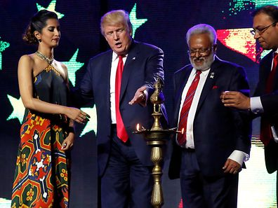 Republican presidential nominee Donald Trump (2nd L) enlists the help of Republican Hindu Coalition Chairman Shalli Kumar (2nd R) and others to light a ceremonial diya lamp before he speaks at a Bollywood-themed charity concert put on by the Republican Hindu Coalition in Edison, New Jersey, on October 15.