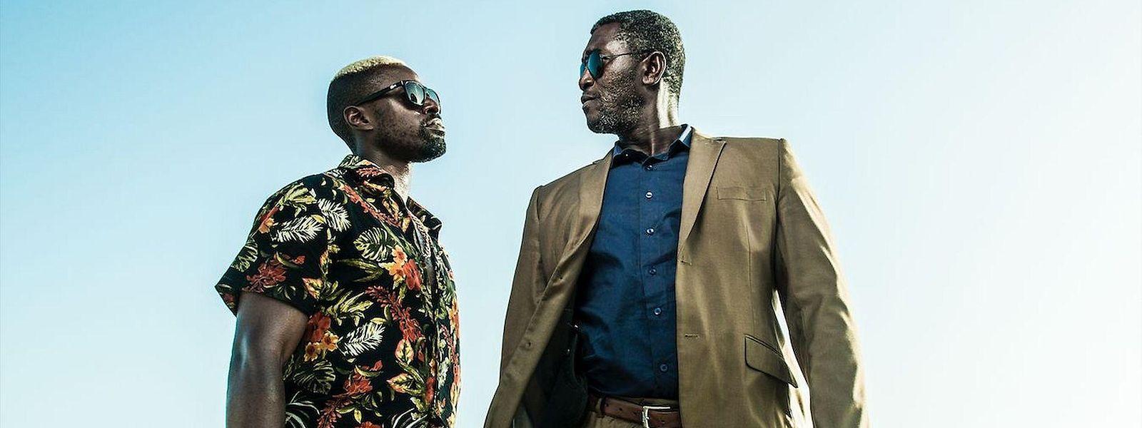 X Basile Mangane (Yann Gael, l.) und Soulaymane Sakho (Issaka Sawadogo) ermitteln in einem ungewöhnlichen Krimiabenteuer in Dakar.