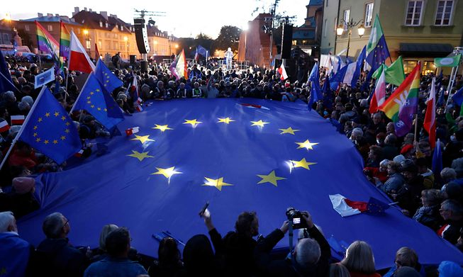 Participants hold a large EU flag as they take part in a pro-EU demonstration in Warsaw on Sunday following a ruling of the Constitutional Court against the primacy of EU law in Poland