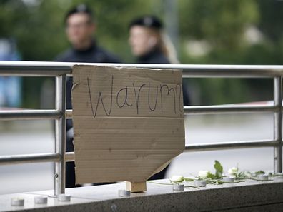A sign reading 'Why' is placed on on a wall near the Olympia shopping mall, where yesterday's shooting rampage started, in Munich.