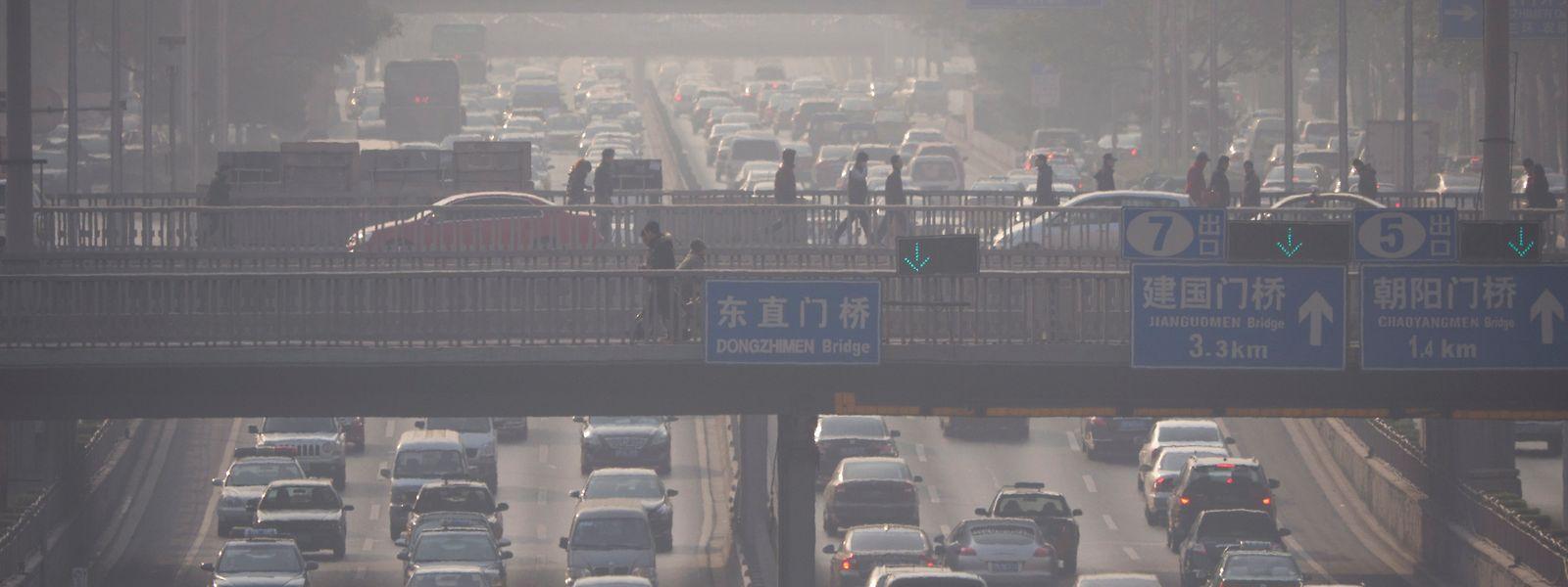 Smog trübt die Sicht über einer sechsspurigen Straße im morgendlichen Berufsverkehr in Peking.