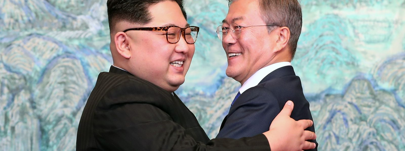 """North Korea's leader Kim Jong Un (L) and South Korea's President Moon Jae-in (R) hug during a signing ceremony near the end of their historic summit at the truce village of Panmunjom on April 27, 2018. The leaders of the two Koreas held a landmark summit on April 27 after a highly symbolic handshake over the Military Demarcation Line that divides their countries, with the North's Kim Jong Un declaring they were at the """"threshold of a new history"""". / AFP PHOTO / Korea Summit Press Pool / Korea Summit Press Pool"""