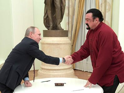Russian President Vladimir Putin (left) shakes hands with US action hero actor Steven Seagal after presenting a Russian passport to him during a meeting at the Kremlin in Moscow.