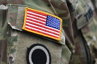 (FILES) In this file photo a US flag is pictured on a soldier's uniform during the 'Dynamic Front 18' exercise in Grafenwoehr, near Eschenbach, southern Germany, on March 7, 2018. - The United States will slash its military presence in Germany by 11,900 troops, relocating some to Italy and Belgium in a major shift of Washington's NATO assets, Defense Secretary Mark Esper announced on July 29, 2020. Of the 34,500 US military personnel in Germany, some 6,400 will be sent home while nearly 5,600 others will be moved to other NATO countries. (Photo by CHRISTOF STACHE / AFP)