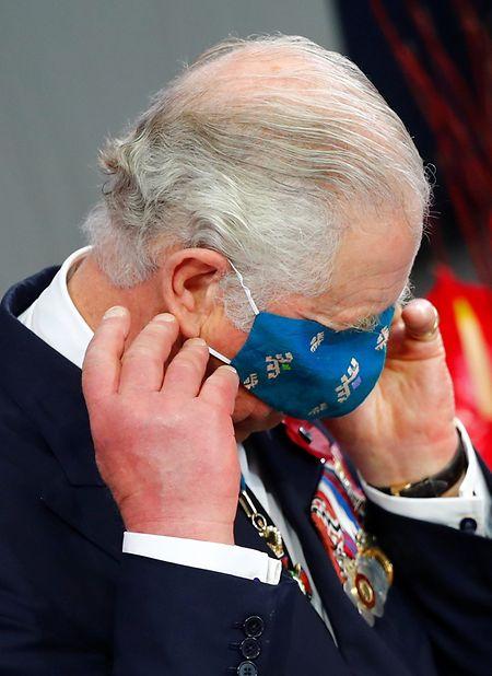 Prinz Charles legt seine Mund-Nasen-Bedeckung im Bundestag nach seiner Gedenkrede zum Volkstrauertag an.