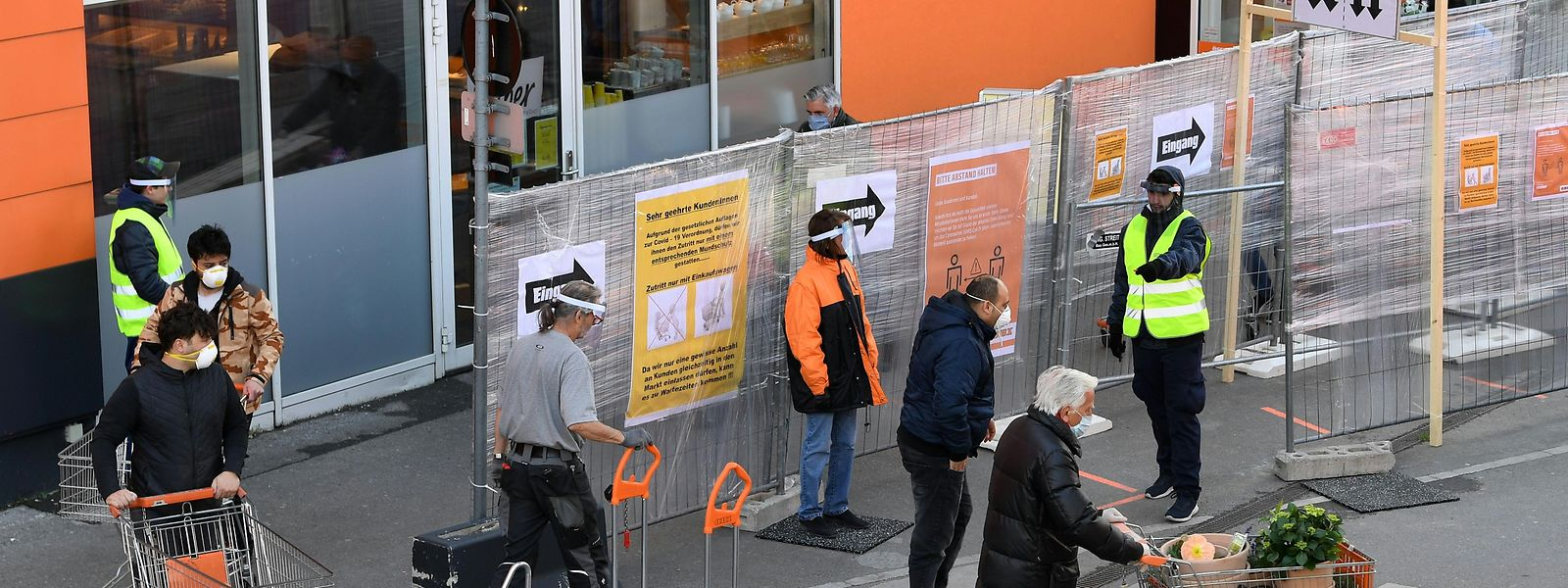 Ein Mitarbeiter (r.) koordiniert Kunden am Eingang eines Baumarktes in Wien. Mit der stufenweise Lockerung der Anti-Corona-Maßnahmen wagt Österreich als eines der ersten Länder in Europa einen Schritt in Richtung Normalität.
