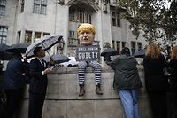 """TOPSHOT - A protester wearing a mask resembling Britain's Prime Minister Boris Johnson holding a """"guilty"""" sign sits on a wall outside the Supreme court in central London on September 24, 2019 after the judgement of the court on the legality of Boris Johnson's advice to the Queen to suspend parliament for more than a month, as the clock ticks down to Britain's October 31 EU exit date. - Britain's Supreme Court on September 24 said that parliamentarians could reconvene """"as soon as possible"""" after ruling that a decision by Prime Minister Boris Johnson to suspend parliament was unlawful. (Photo by Tolga AKMEN / AFP)"""
