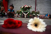TOPSHOT - Children sit next to flowers left by mourners near St. Anthony's Shrine in Colombo on April 23, 2019, two days after a series of bomb blasts targeting churches and luxury hotels in Sri Lanka. - Sri Lanka began a day of national mourning on April 23 with three minutes of silence to honour more than 300 people killed in suicide bomb blasts that have been blamed on a local Islamist group. (Photo by Jewel SAMAD / AFP)