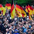 "Demonstrators hold flags of Germany during a protest organised by the right-wing populist ""Pro Chemnitz"" movement, the far-right Alternative for Germany (AfD) party and the anti-Islam Pegida movement, on September 1, 2018 in Chemnitz, eastern Germany. - The demonstration was organised in a reaction to a knife killing, allegedly by an Iraqi and a Syrian, that set off anti-immigrant mob violence. (Photo by John MACDOUGALL / AFP)"