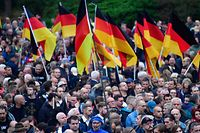 """Demonstrators hold flags of Germany during a protest organised by the right-wing populist """"Pro Chemnitz"""" movement, the far-right Alternative for Germany (AfD) party and the anti-Islam Pegida movement, on September 1, 2018 in Chemnitz, eastern Germany. - The demonstration was organised in a reaction to a knife killing, allegedly by an Iraqi and a Syrian, that set off anti-immigrant mob violence. (Photo by John MACDOUGALL / AFP)"""