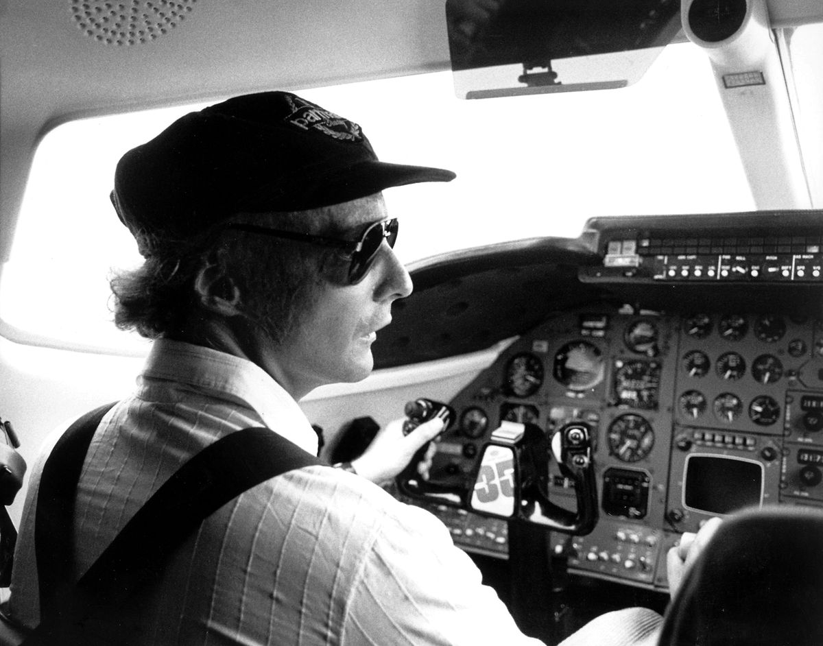 Diese historische Aufnahme zeigt den ehemaligen Formel-1-Piloten Niki Lauda im Cockpit eines Flugzeugs.