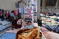 """A migrant rests on a makeshift bed under a placard reading """"clandestinity kills, live in dignity or die"""" during the occupation of  St. John the Baptist Church at the B�guinage, in the center of Brussels on June 20, 2021. - Undocumented migrants, some of them having started an hunger strike, have occupied the 17th-century church since the end of January to denounce their lack of rights in Belgium and to call calling for a legal status. (Photo by JOHN THYS / AFP)"""