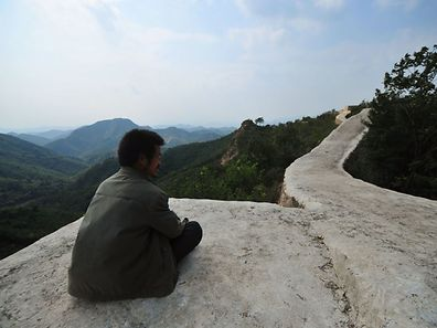 "This picture taken on September 21, 2016 shows a villager sitting on a paved-over section of the Great Wall of China at Suizhong, in China's northeast Liaoning province. Chinese social media users were in an uproar on September 23 over restoration of a 700-year-old section of the Great Wall that has been covered in concrete, turning it into a smooth, flat-topped path. Known as one of the most beautiful portions of the ""wild"", unrestored wall, the eight-kilometre (five-mile) Xiaohekou stretch in northeast Liaoning province was built in 1381 during the Ming Dynasty. / AFP PHOTO / STR / China OUT"