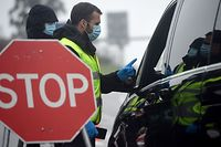 Checkpoint personnel and Portuguese National Republican Guards talk to a driver at a checkpoint in the Portuguese-Spanish border crossing between Valenca and Tui on January 31, 2021. - Portugal imposed controls on its border with Spain in an attempt to contain the spread of the coronavirus pandemic. Travel abroad will be limited for two weeks starting today. (Photo by MIGUEL RIOPA / AFP)