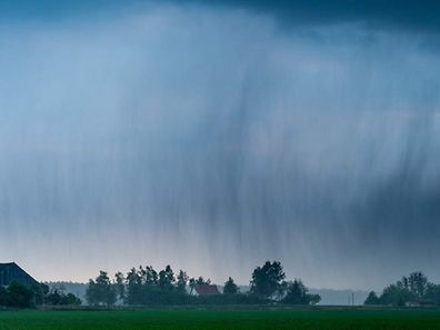 TOPSHOT - A thunder cell bringing heavy rain and hail hangs over a field near Neuhardenberg, northeastern Germany, on May 24, 2016. / AFP PHOTO / dpa / Patrick Pleul / Germany OUT