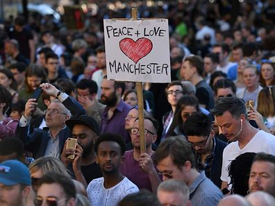 TOPSHOT - People attend a vigil in Albert Square in Manchester, northwest England on May 23, 2017, in solidarity with those killed an injured in the May 22 terror attack at the Ariana Grande concert at the Manchester Arena. Twenty two people have been killed and dozens injured in Britain's deadliest terror attack in over a decade after a suspected suicide bomber targeted fans leaving a concert of US singer Ariana Grande in Manchester. British police on Tuesday named the suspected attacker behind the Manchester concert bombing as Salman Abedi, but declined to give any further details. / AFP PHOTO / Ben STANSALL