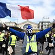 """A protester wearing a luchador mask waves a French flag during a 20th consecutive saturday of demonstrations called by the """"yellow vests"""" (gilets jaunes) movement on March 30, 2019, at the Gare de L'Est in Paris. - The """"yellow vest"""" movement - so-called after the protesters' high-visibility jackets - began nationwide five months ago over fuel taxes but quickly grew into a broader wave to protest against French President's policies and his top-down style of governing, high cost of living, government tax reforms and for more """"social and economic justice."""" (Photo by STEPHANE DE SAKUTIN / AFP)"""