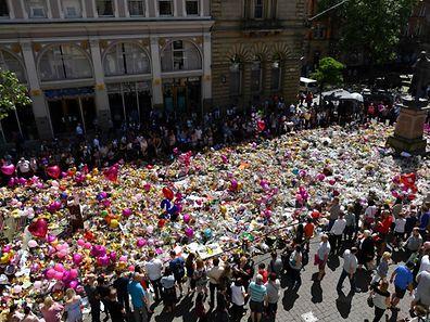 La Place St Ann, devenue emblématique de l'affliction des Mancuniens, les fleurs s'amassent et débordent.