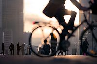 Morning image of businessman on bicycle passing skyline of La Defense business district in Paris, France.