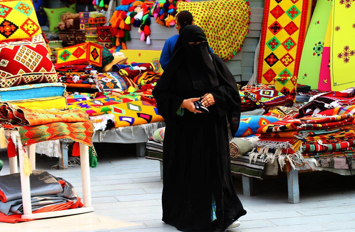 Eine Katari-Frau im Souq Waqif in Doha. Unter der Abaya tragen viele Frauen Luxusmode im westlichen Stil.