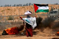 A woman stands holding a Palestinian flag with a cloth sack placed above her head before a barbed-wire fence and next to burning tires, during clashes following a demonstration near the border with Israel east of Khan Yunis in the southern Gaza Strip on June 8, 2018. / AFP PHOTO / SAID KHATIB