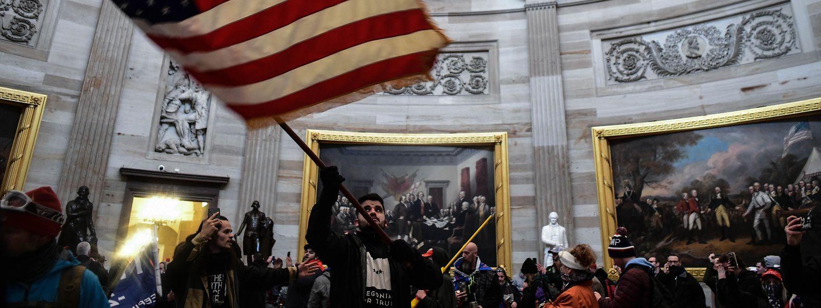 Ein Demonstrant schwenkt die US-Flagge im Inneren des Kapitols, nachdem Anhänger von US-Präsident Donald Trump das Gebäude gestürmt hatten.
