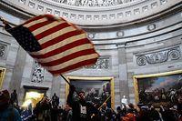 06.01.2021, USA, Washington: Ein Demonstrant schwenkt die US-Flagge im Inneren des US-Kapitols, nachdem Anhänger von US-Präsident Donald Trump das Gebäude gestürmt hatten, in dem die Abgeordneten den Sieg des designierten Präsidenten Joe Biden bei der Wahl im November bestätigen sollten. Foto: Miguel Juarez Lugo/Zuma Press/dpa +++ dpa-Bildfunk +++