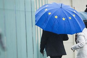 A man holding an umbrella in the colours of the European Union enters the chancellery in Berlin before talks between government and opposition leaders about the EU fiscal pact June 21, 2012. Germany's small Left Party said it would lodge a complaint with the constitutional court in an attempt to prevent ratification of the European Union's fiscal pact, which the Berlin government has championed, and the ESM permanent bailout scheme. 