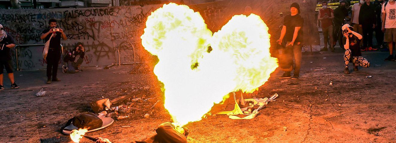 19. Oktober:  Ein Demonstrant spuckt Feuer in Form eines Herzens während einer Demonstration zum zweiten Jahrestag der Unruhen gegen soziale Ungleichheit in Santiago de Chile.