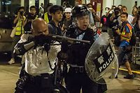 A police officer (L) points a firearm during a clash with protesters who had gathered outside Kwai Chung police station, in support of protesters detained with the charge of rioting, in Hong Kong late on July 30, 2019. - Renewed clashes broke out between pro-democracy protesters and police in Hong Kong late on July 30 after dozens of demonstrators were charged with rioting -- an offence that carries a jail term of up to ten years. (Photo by ISAAC LAWRENCE / AFP)