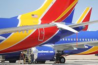 VICTORVILLE, CA - MARCH 27: Workers stand beneath Southwest Airlines Boeing 737 MAX aircraft parked at Southern California Logistics Airport on March 27, 2019 in Victorville, California. Southwest Airlines is waiting out a global grounding of MAX 8 and MAX 9 aircraft at the airport.   Mario Tama/Getty Images/AFP == FOR NEWSPAPERS, INTERNET, TELCOS & TELEVISION USE ONLY ==