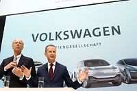 """(ALTERNATIVE CROP) This photo taken on April 13, 2018 shows then newly appointed CEO of German car maker Volkswagen (VW) Herbert Diess (R) and VW supervisory board chairman Hans Dieter Poetsch giving a press conference at the company's headquarters in Wolfsburg, central Germany. - Volkswagen announced on May 19, 2020 to end one of the most potentially damaging cases in its """"Dieselgate"""" scandal, paying 9 million euros in an out-of-court settlement to prevent its two bosses going to trial over market manipulation charges. The German car giant's chief executive Herbert Diess and supervisory board chief Hans Dieter Poetsch were in September 2019 charged for allegedly failing to inform shareholders in a timely manner about the pollution cheating scandal in 2015. (Photo by Odd ANDERSEN / AFP) / ALTERNATIVE CROP"""