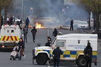 Belfast: Eine Frau mit Kinderwagen läuft an Fahrzeugen der Sicherheitskräfte und Demonstranten während Unruhen am Lanark Way vorbei.