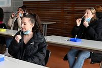 Student of a graduating class at the Geschwister-Scholl school in Tuebingen, southern Germany,, conduct an antigen rapid test for COVID-19 in a class room on February 11, 2021 amid the ongoing new coronavirus pandemic. - In collaboration with the city of Tuebingen the school tests teachers and students of the graduating classes regulary free to ensure present teaching in the class room instead of online teaching. (Photo by THOMAS KIENZLE / AFP)