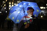 "A pro-EU supporter shelters under a European flag umbrella beside the Houses of Parliament in Westminster, central London on January 14, 2019. - Prime Minister Theresa May on Monday published further assurances from the EU on the eve of a crucial parliamentary vote on her Brexit deal and warned MPs that rejecting it would lead to ""paralysis"" that could see Britain stay in the bloc. (Photo by Daniel LEAL-OLIVAS / AFP)"